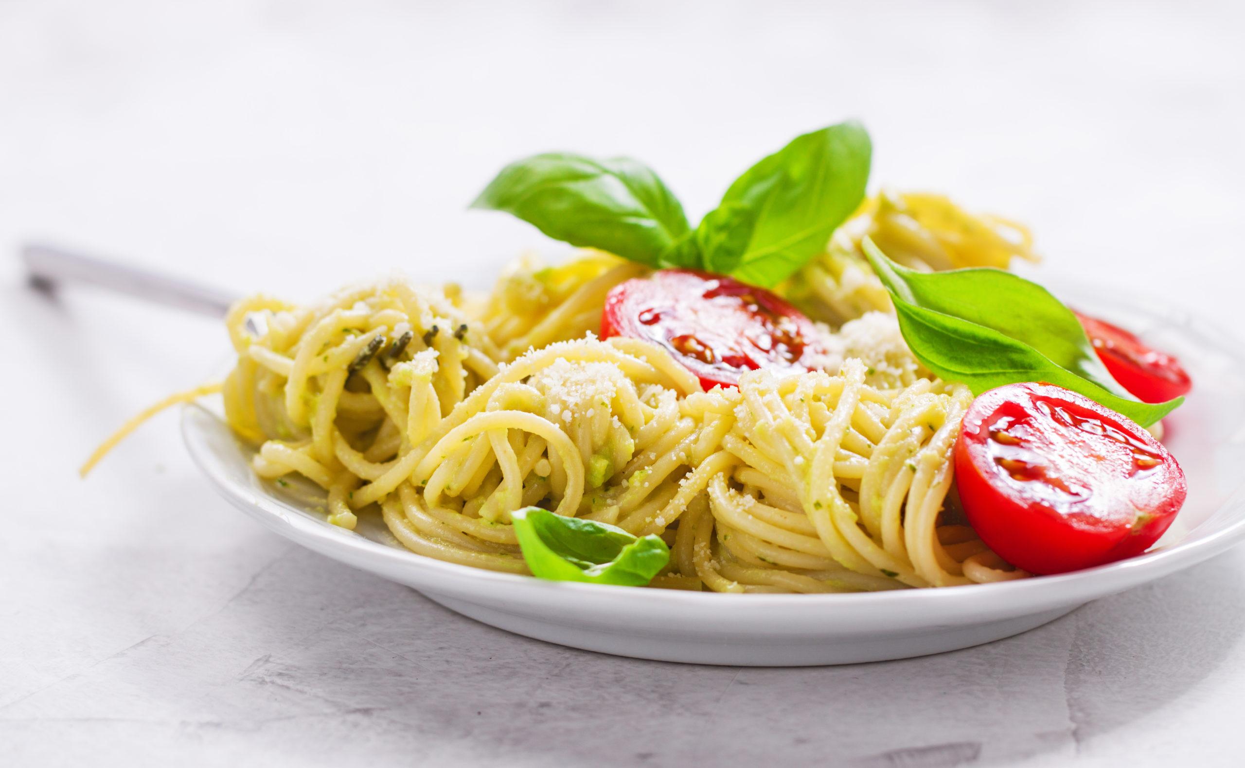 Homemade spaghetti pasta with avocado, tomato and basil sauce, closeup